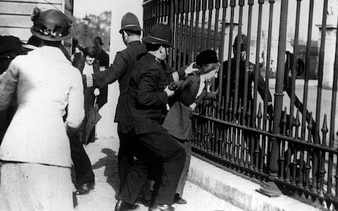 A policeman restrain a demonstrator as suffragettes gathered outside Buckingham Palace in 1914. Suffragettes campaigned vigorously in the early part of the 2Oth century to gain the right for women to vote, and one died in 1913 when she threw herself under the King's horse at the Derby. - Credit: PA/PA