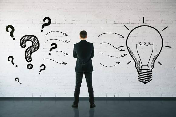 A man standing in front of a wall drawing showing question marks connected to a light bulb by several wavy arrows.