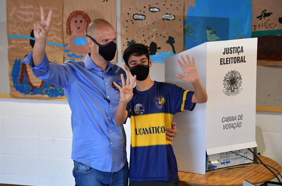 Sao Paulo's Mayor Bruno Covas (L) poses with his son Tomas at a polling station during the municipal election runoff in Sao Paulo, Brazil, on November 29 2020, amid the new coronavirus pandemic. - Brazilians go to the polls Sunday to chose mayors in 57 cities, including Sao Paulo and Rio de Janeiro, the most rich and populated, in a runoff marked by the economic crisis and an upsurge of the new coronavirus. (Photo by NELSON ALMEIDA / AFP) (Photo by NELSON ALMEIDA/AFP via Getty Images)