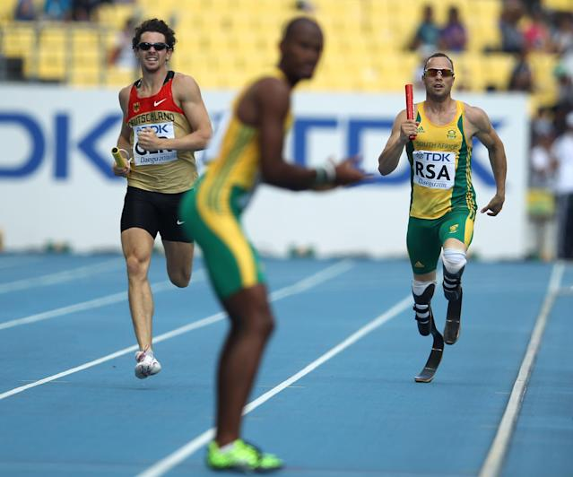 DAEGU, SOUTH KOREA - SEPTEMBER 01: (R-L) Oscar Pistorius of South Africa runs towards teammate Ofentse Mogawane during the men's 4x400 metres relay heats during day six of the 13th IAAF World Athletics Championships at the Daegu Stadium on September 1, 2011 in Daegu, South Korea. (Photo by Chris McGrath/Getty Images)