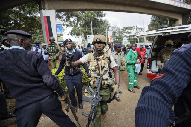 A member of Kenyan special forces shouts at the media to go back after his wounded colleague was carried into an ambulance by paramedics at the scene Wednesday, Jan. 16, 2019 in Nairobi, Kenya. Extremists stormed a luxury hotel in Kenya's capital on Tuesday, setting off thunderous explosions and gunning down people at cafe tables in an attack claimed by Africa's deadliest Islamic militant group. (AP Photo/Ben Curtis)