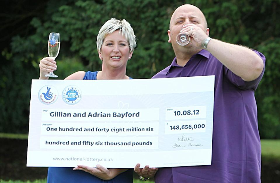 Adrian Bayford and wife Gillian seen celebrating with a giant cheque.