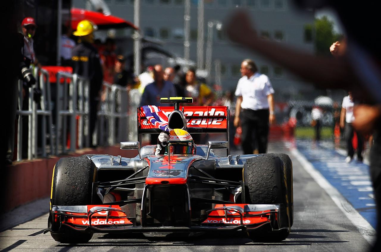 MONTREAL, CANADA - JUNE 10:  Lewis Hamilton of Great Britain and McLaren waves the Union Jack flag in celebration as he drives down the pitlane after winning the Canadian Formula One Grand Prix at the Circuit Gilles Villeneuve on June 10, 2012 in Montreal, Canada.  (Photo by Paul Gilham/Getty Images)