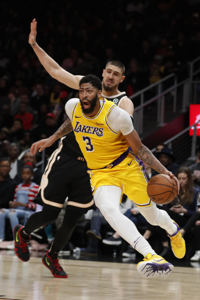 Los Angeles Lakers forward Anthony Davis (3) drives past Atlanta Hawks center Alex Len in the second half of an NBA basketball game Sunday, Dec. 15, 2019, in Atlanta. Los Angles won 101-96.(AP Photo/John Bazemore)