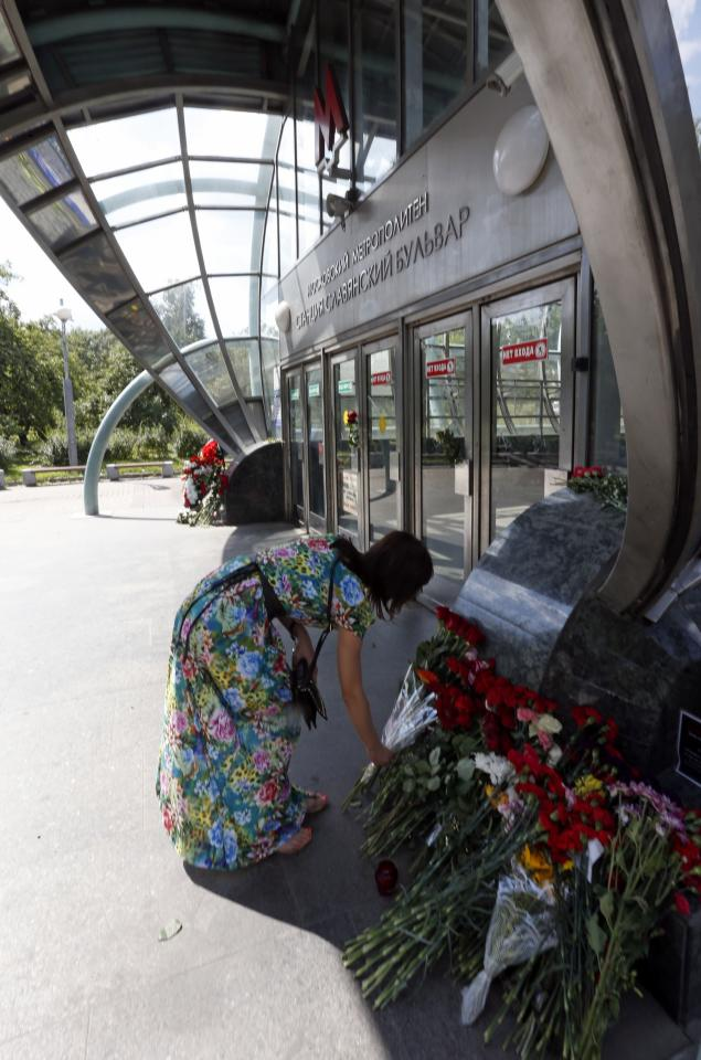 A woman lays flowers in memory of victims of Tuesday's accident, in which three carriages derailed on a train during morning rush hour, at the entrance to a metro station in Moscow July 16, 2014. Russian state investigators said on Wednesday they had detained two Moscow metro workers suspected of safety breaches that may have caused an accident that killed at least 21 people. REUTERS/Sergei Karpukhin (RUSSIA - Tags: TRANSPORT DISASTER)