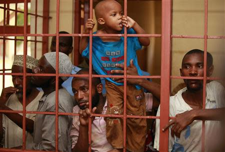 A boy, who was with fellow Muslims detained by police from Sunday's raid at the Masjid Mussa mosque, climb in a cell as the men wait to be arraigned at a court in Shanzu, a coastal town of Mombasa February 3, 2014. REUTERS/Joseph Okanga