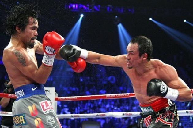 Manny Pacquiao (L) and Juan Manuel Marquez battle during their welterweight fight at the MGM Grand Garden in Las Vegas, Nevada. Marquez knocked out Pacquiao in the 6th round. Pacquiao says he welcomes another fight with Marquez, one that would put them into an elite class of boxing champions
