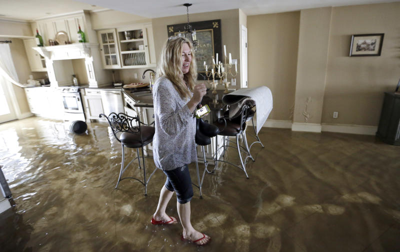 Becky Melkin reacts as she returns to her home to see the damage caused by Isaac in the West End Park neighborhood along Lake Pontchartrain, Friday, Aug. 31, 2012 in New Orleans. Isaac crawled into the central U.S. on Friday, leaving behind a soggy mess in Louisiana. It will be a few days before the water recedes and people in flooded areas can return home. New Orleans itself was spared, thanks in large part to a levee system fortified after Katrina devastated the Gulf Coast in 2005. (AP Photo/David J. Phillip)