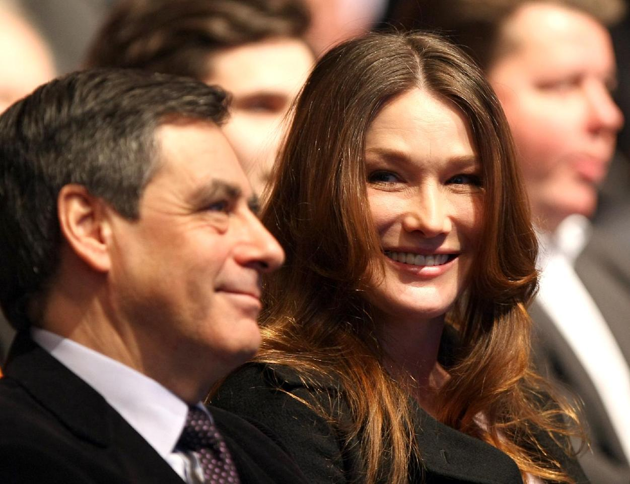 Wife of France's President and Candidate for the Presidential Election 2012, Nicolas Sarkozy, Carla Bruni Sarkozy, right, speaks with First Minister Francois Fillon, at a meeting in Marseille, southern France, Sunday, Feb. 19, 2012. Sarkozy has thrown himself into what may be the toughest fight of his political career: unpopular for years and running a feeble economy, the divisive French president announced he's running for a second term. (AP Photo/Claude Paris)
