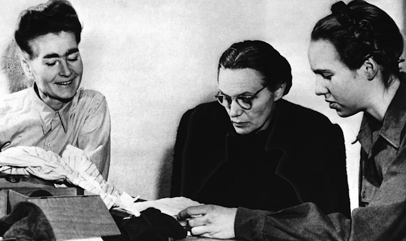 FILE - The Jan 1, 1946 file photo shows Margarete Himmler, wife of the German S.S. Chief who committed suicide, centre, as she reads over some papers with her daughter Gudrun, right, as they are watched by Louise Cuyon-Witzschel, who was secretary at the S.S. Headquarters in Italy, at Nuremberg, Germany, where they are waiting to testify in the trial of Major Nazi War Criminals. German newspaper Welt am Sonntag has published a trove of letters believed to be written by Nazi SS leader Heinrich Himmler. On seven full pages the paper on Sunday Jan. 26,2014 showed pictures of Himmler and his family smiling into the camera during a fishing trip, the top Nazi taking a bath in a lake or feeding a little fawn. Welt said it worked together with Israeli film director Vanessa Lapa, whose family had the documents in its possession. (AP Photo,File)