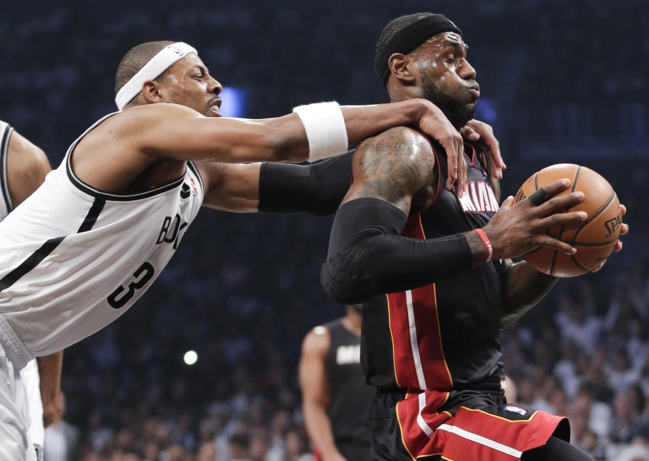 Brooklyn Nets forward Paul Pierce (34) fouls Miami Heat forward LeBron James (6) as he drives through the lane to score in the first period during Game 3 of an Eastern Conference semifinal NBA playoff basketball game on Saturday, May 10, 2014, in New York. Pierce was called for a flagrant foul and James scored on the play. (AP Photo/Julie Jacobson)