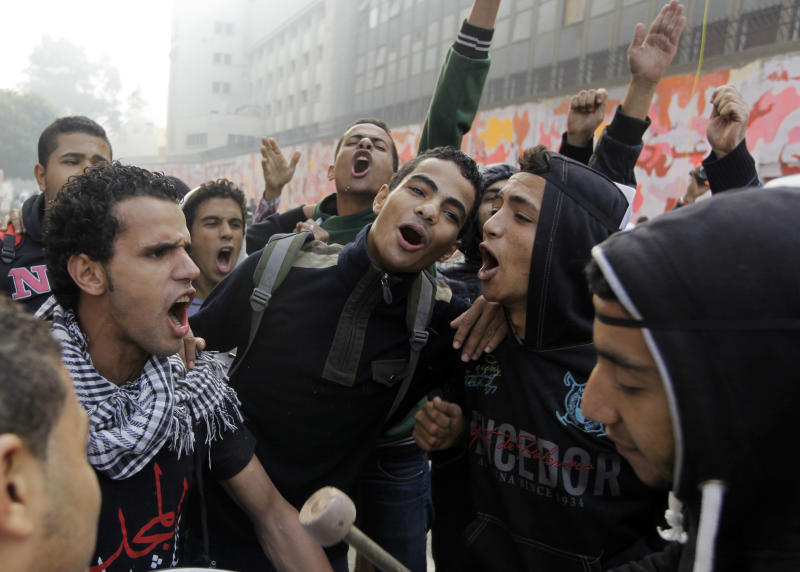 Egyptians chant anti-police slogans at the entrance of Mohammed Mahmoud street near Tahrir Square, Cairo, Egypt, Tuesday, Nov. 19, 2013. Egypt's revolutionary groups will mark Tuesday the second anniversary of some of the fiercest confrontations between Egyptian protesters and security forces in Mohammed Mahmoud street where scores had been killed. Rallies are also expected later in the day amid fears of more unrest and violence. (AP Photo/Amr Nabil)