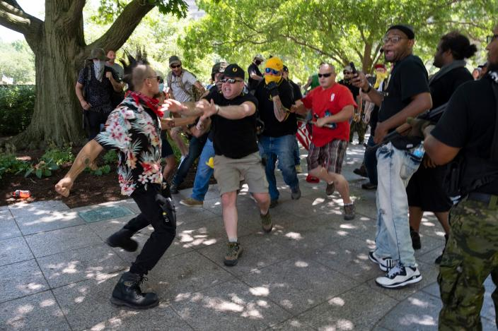 "A member of the ""boogaloo"" movement, left, gets into a physical altercation with members of the Proud Boys during a right-wing protest in Columbus, Ohio, on July 18. (Jeff Dean/AFP via Getty Images)"