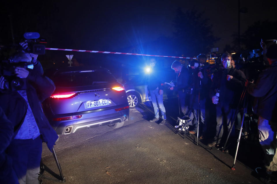 A police car enters the perimeter after a history teacher who opened a discussion with students on caricatures of Islam's Prophet Muhammad was decapitated, Friday, Oct. 16, 2020 in Conflans-Saint-Honorine, north of Paris. Police have shot the suspected killer dead. (AP Photo/Michel Euler)