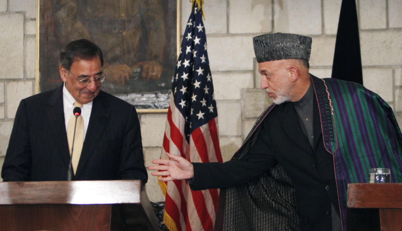 Afghan President Hamid Karzai, right, gestures towards U.S. Defense Secretary Leon Panetta ahead of  starting a joint press conference at the presidential palace in Kabul, Afghanistan, Wednesday, Dec. 14, 2011. (AP Photo/Musadeq Sadeq)
