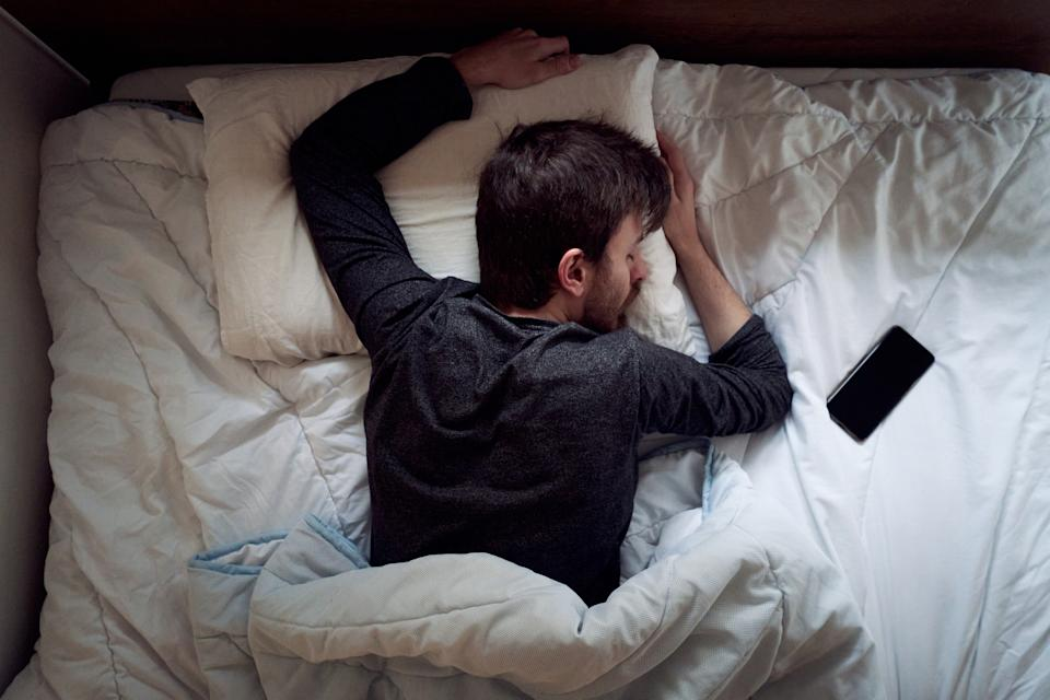Young male sleeping in the bed only himself during the day smartphone next to him