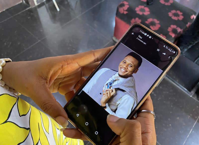Onomene Adene shows a picture of her brother on a mobile phone during an interview with Reuters in Lagos
