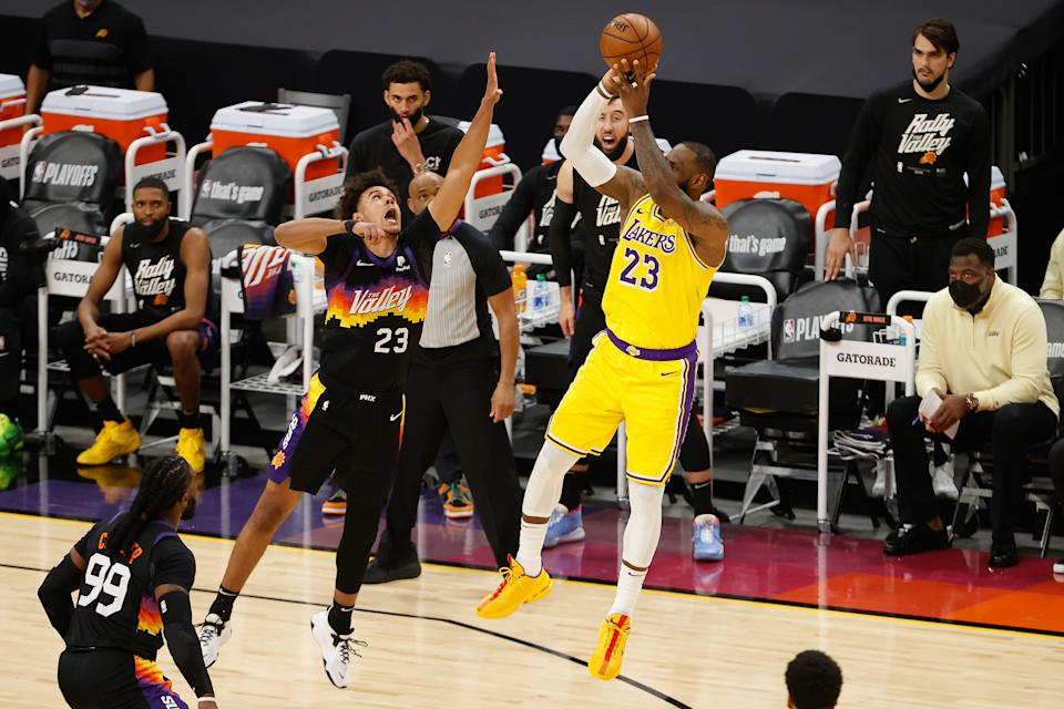 PHOENIX, ARIZONA - MAY 25: LeBron James #23 of the Los Angeles Lakers attempts a three-point shot over Cameron Johnson #23 of the Phoenix Suns during the second half of Game Two of the Western Conference first-round playoff series at Phoenix Suns Arena on May 25, 2021 in Phoenix, Arizona. NOTE TO USER: User expressly acknowledges and agrees that, by downloading and or using this photograph, User is consenting to the terms and conditions of the Getty Images License Agreement.  (Photo by Christian Petersen/Getty Images)