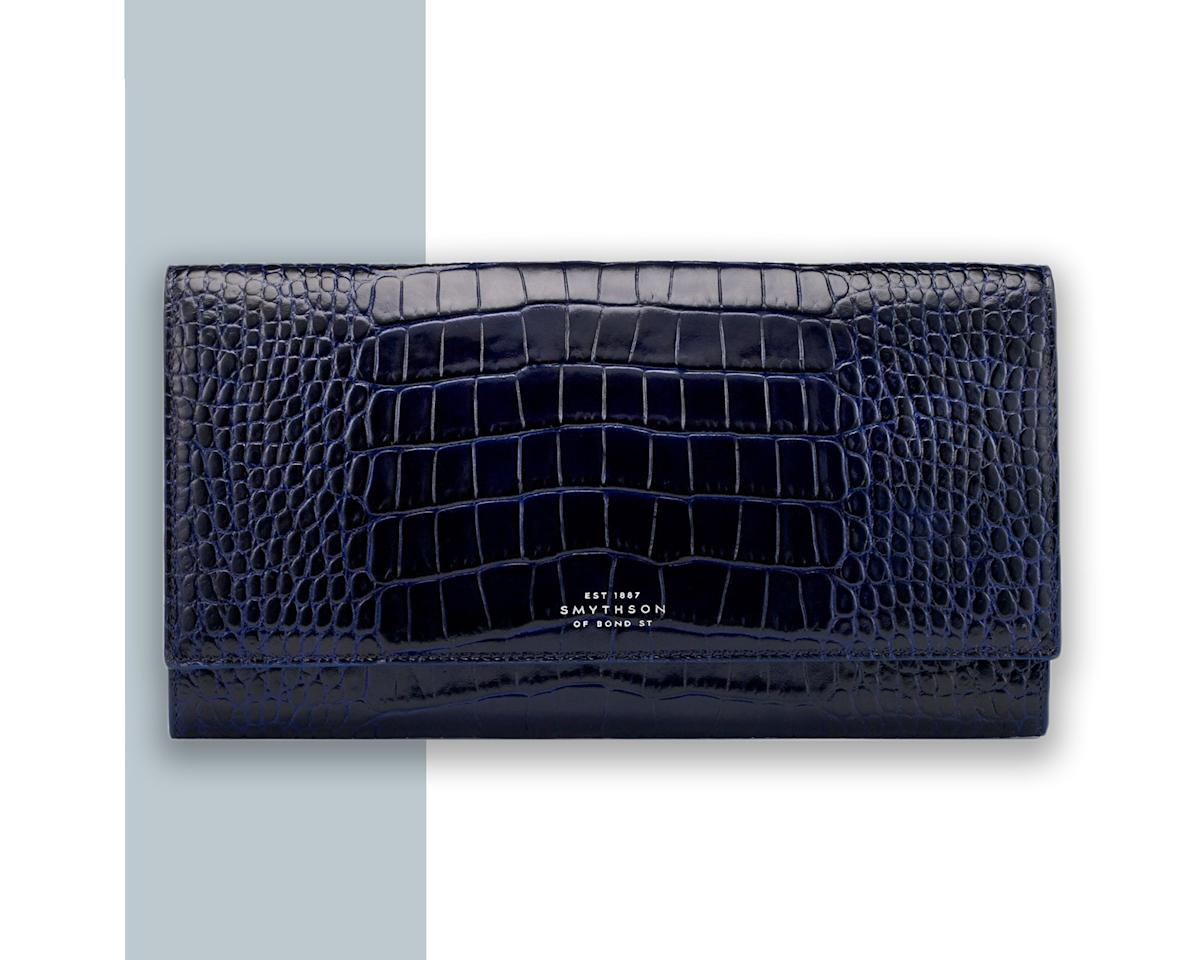 """<p>It doesn't get more organized than this Smythson wallet specifically designed for international travel. It has clearly marked compartments for each category: currency, boarding pass, tickets, passport, and the odds and ends that fall under """"other."""" And with a shiny navy croc-embrossed exterior and a luxe satin interior, it doesn't get much chicer either.</p> <p><strong>Buy Now</strong>: <a href=""""https://fave.co/2YK9Q02"""" rel=""""nofollow"""">$550, smythson.com</a></p>"""