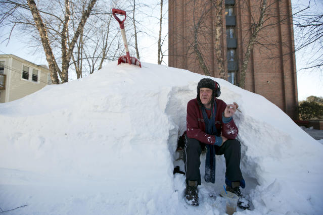 Bert Johnson takes a break while clearing snow from a bus-stop bench outside the apartment complex where he lives in Portland, Maine, Sunday, Feb. 10, 2013. Residents are digging out after a blizzard dumped a record 31.9 inches of snow on the city. (AP Photo/Robert F. Bukaty)