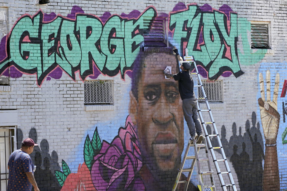 In this Sunday, June 7, 2020, photo, Zack Murray paints a mural honoring George Floyd, on the side of a building in Houston's Third Ward. Floyd, who grew up in the Third Ward, died after being restrained by Minneapolis police officers on Memorial Day. (AP Photo/David J. Phillip)