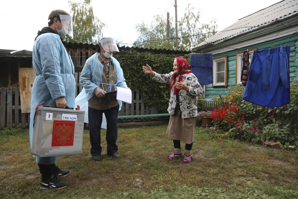 Members of an election commission listen to 82-year old Nadezhda Tredina, as they come to help her to vote during the Parliamentary elections at her house in Nikolayevka village outside Omsk, Russia, Saturday, Sept. 18, 2021. Sunday will be the last of three days voting for a new parliament, but there seems to be no expectation that United Russia, the party devoted to President Vladimir Putin, will lose its dominance in the State Duma. (AP Photo/Evgeniy Sofiychuk)