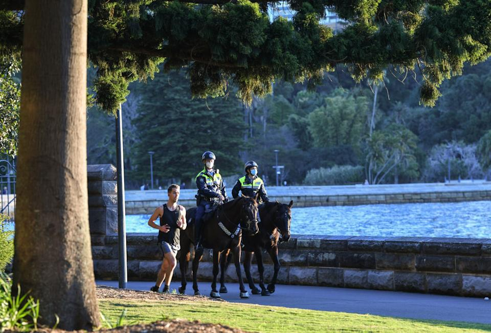 Two mounted police officers patrol around the edge of the harbour as a man runs past them doing his permitted exercise in Sydney, Australia.