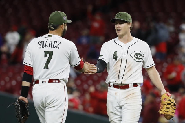 Cincinnati Reds first baseman Brandon Dixon (4) celebrates with third baseman Eugenio Suarez (7) after closing the ninth inning of a baseball game, Tuesday, Sept. 11, 2018, in Cincinnati. The Reds won 3-1. (AP Photo/John Minchillo)