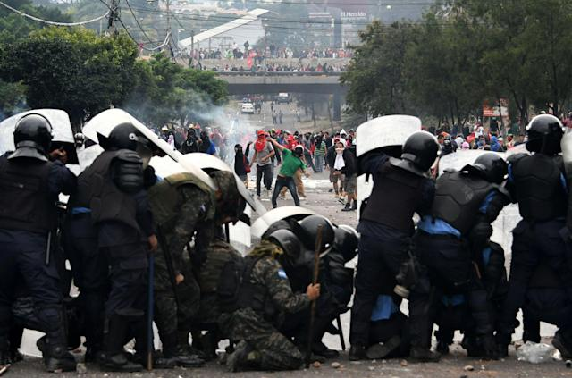 <p>Supporters of Honduran presidential candidate for the Opposition Alliance against the Dictatorship coalition, Salvador Nasralla, clash with soldiers and riot police near the Electoral Supreme Court (TSE), as the country waits for the final results of the week-end's presidential election, in Tegucigalpa, on Nov. 30, 2017. (Photo: Orlando Sierra/AFP/Getty Images) </p>