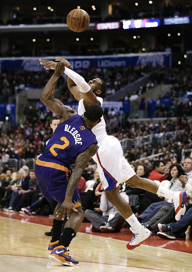 Los Angeles Clippers' Chris Paul is fouled by Phoenix Suns' Eric Bledsoe (2) during the first half of an NBA basketball game on Monday, Dec. 30, 2013, in Los Angeles. (AP Photo/Jae C. Hong)