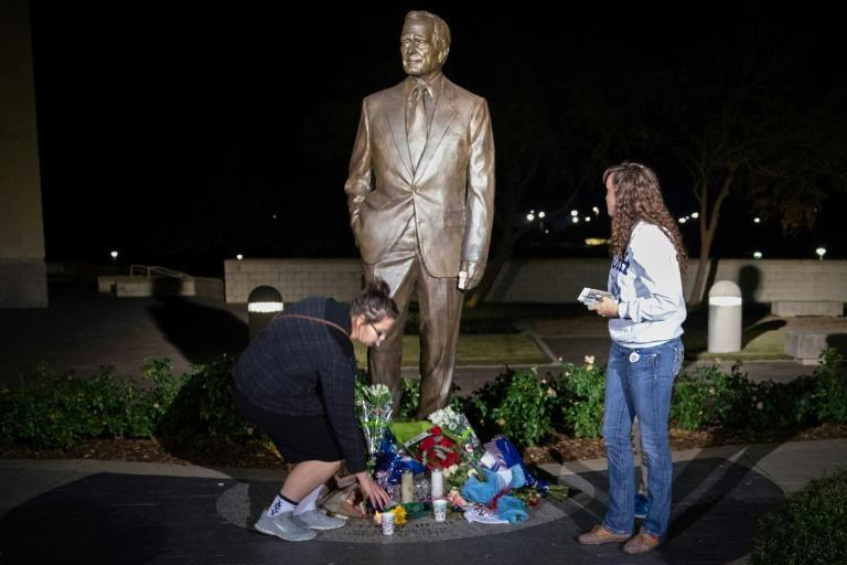 Mourners place candles at the foot of a statue of George Bush at his presidential library in College Station, Texas, where he will be laid to rest next week