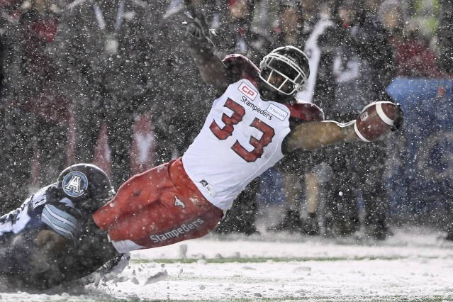 Calgary Stampeders running back Jerome Messam (33) is tackled by Toronto Argonauts linebacker Terrance Plummer (47) as he scores a touchdown during the first half of a CFL football game in the Grey Cup in Ottawa on Sunday, Nov. 26, 2017. (Sean Kilpatrick/The Canadian Press via AP)