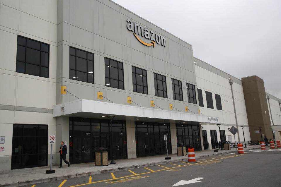A man leaves an Amazon fulfillment center, Thursday, March 19, 2020, on Staten Island, in New York. The company is hiring 100,000 new workers at it's fulfillment and distribution centers to meet increased consumer demand during the current coronavirus outbreak. (AP Photo/Kathy Willens)