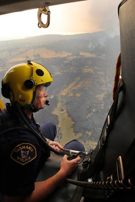 This aerial photograph taken on January 5, 2013 shows Westpac Police Rescue Helicopter crewman Sgt. Matthew Drumm surveying the devastated town of Dunalley after bush fires swept through the area.  Thousands of people have fled wildfires raging on the Australian island of Tasmania that have destroyed at least 80 properties amid fears that at least one man died in the blaze, police said.  AFP PHOTO / POOL / Chris Kidd