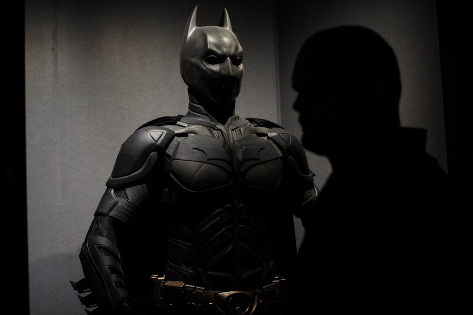 LONDON, ENGLAND - FEBRUARY 22: A visitor walks past a Batman costume from the 2012 Dark Knight Rises film worn by Christian Bale and designed by Lindy Hemming is on display at the DC Comics Exhibition: Dawn Of Super Heroes at the O2 Arena on February 22, 2018 in London, England. The exhibition, which opens on February 23rd, features 45 original costumes, models and props used in DC Comics productions including the Batman, Wonder Woman and Superman films. (Photo by Jack Taylor/Getty Images)