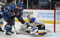 St. Louis Blues goaltender Jordan Binnington, right, makes a save against a shot by Colorado Avalanche left wing Andre Burakovsky (95) in the second period of Game 1 of an NHL hockey Stanley Cup first-round playoff series Monday, May 17, 2021, in Denver. (AP Photo/David Zalubowski)