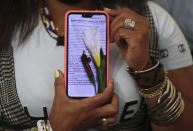 Community leader Luz Nelly Santana shows one of the many death threats she has received in Bogota, Colombia, Thursday, Dec. 17, 2020. The Afro-Colombian community leader sometimes uses a hat or a turban to disguise herself and always wears a bulletproof vest. (AP Photo/Fernando Vergara)