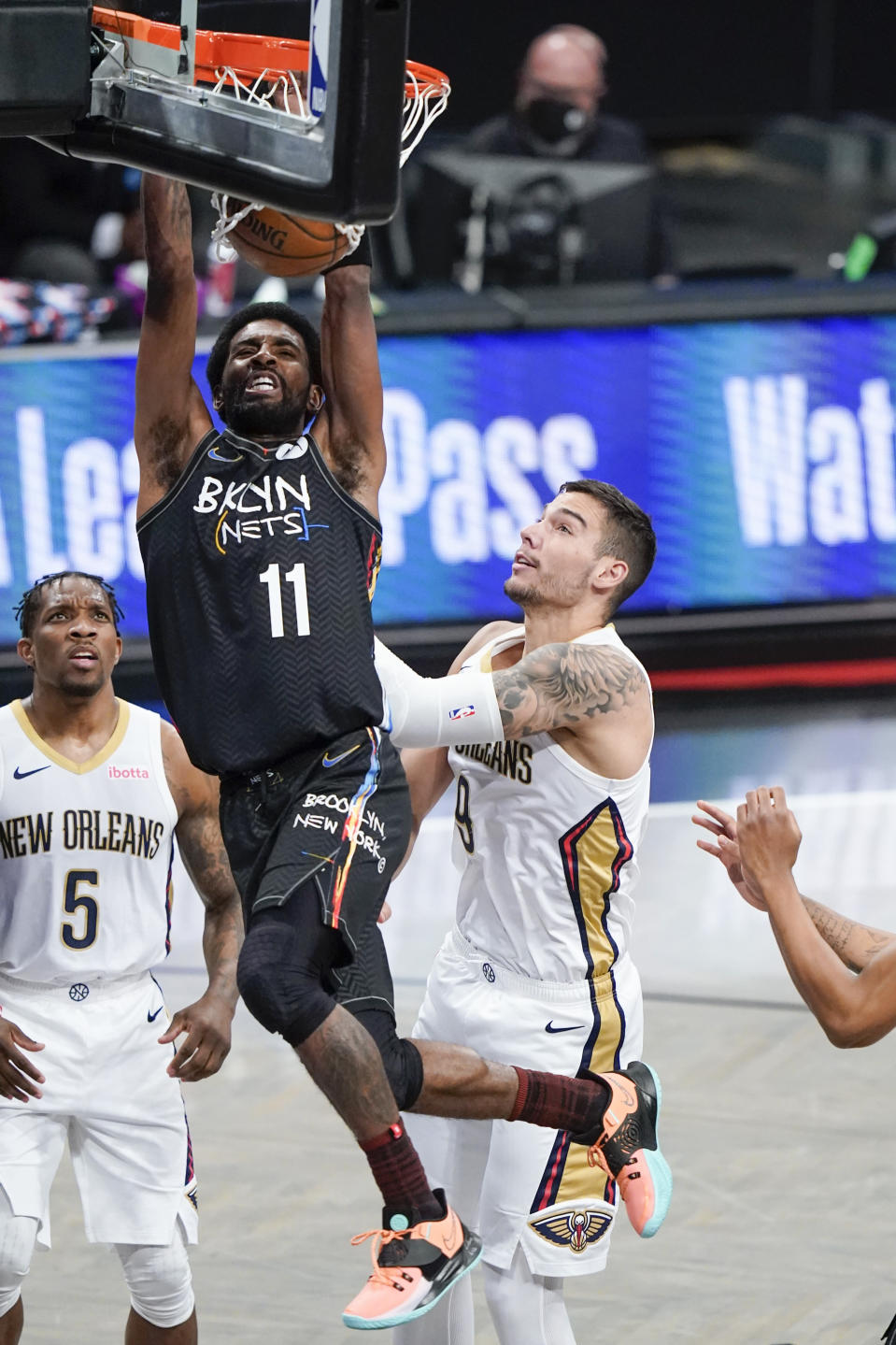 Brooklyn Nets' Kyrie Irving (11) dunks the ball in front of New Orleans Pelicans' Eric Bledsoe (5) and Willy Hernangomez (9) during the first half of an NBA basketball game Wednesday, April 7, 2021, in New York. (AP Photo/Frank Franklin II)