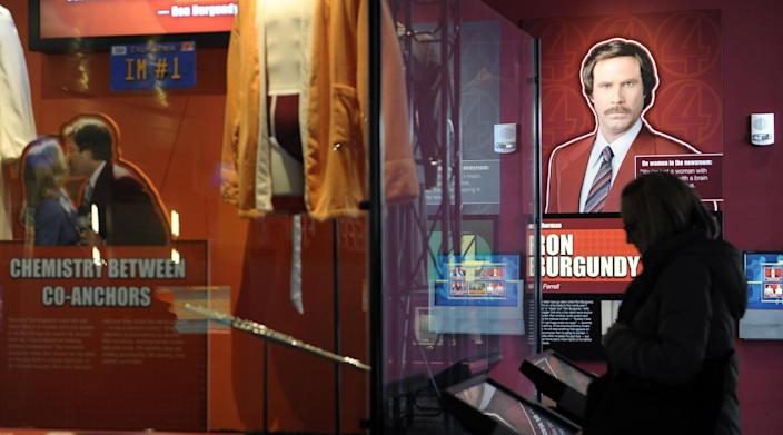 """A Newseum visitor looks at the """"Anchorman"""" movie exhibit at the Newseum in Washington, Friday, Nov. 15, 2013. The museum about news and the First Amendment has opened """"Anchorman: The Exhibit,"""" featuring costumes and props from Will Ferrell's 2004 movie """"Anchorman: The Legend of Ron Burgundy."""" The story of a fictional news team's sexist reaction to the arrival of an ambitious female reporter was a parody of real tumult in the 1970s TV business. (AP Photo/Susan Walsh)"""