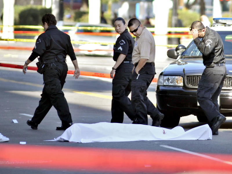 """Investigators look at a body at the scene of a fatal shooting, Friday,  Dec. 9, 2011, in the Hollywood are of Los Angeles, Calif. A gunman who fired at cars and shouted """"kill me"""" and """"I'm gonna die!"""" was shot to death Friday by police after wounding a driver in the heart of Hollywood, authorities and a witness reported. (AP Photo/Josh Edelson)"""