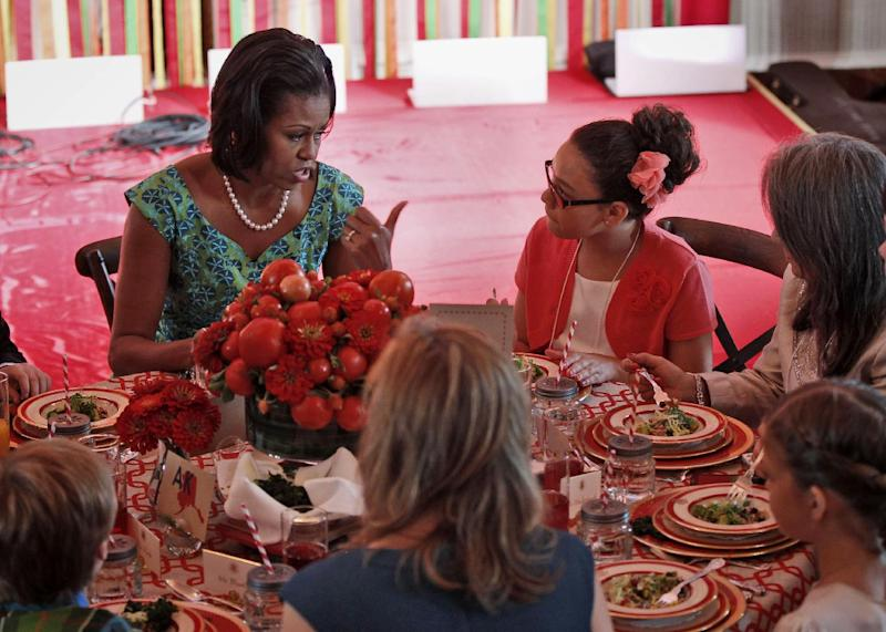 """FILE - This Aug. 20, 2012 file photo shows first lady Michelle Obama talking with Illana Gonzalez-Evans, from Washington, during the Kids' """"State Dinner,"""" in the East Room of the White House in Washington. Michelle Obama will welcome 54 children to the White House on July 9 for creating winning recipes as part of a healthy lunch contest. The winners will dine on some of the winning dishes at the second kids' """"state dinner"""" and tour the White House vegetable garden. """"The X Factor"""" alum singer Rachel Crow will also perform. (AP Photo/Pablo Martinez Monsivais, File)"""