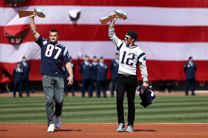 Rob Gronkowski #87 and Tom Brady #12 of the New England Patriots enter the field carrying Vince Lombardi trophies before the opening day game between the Boston Red Sox and the Pittsburgh Pirates at Fenway Park on April 3, 2017 in Boston, Massachusetts. (Photo by Maddie Meyer/Getty Images)