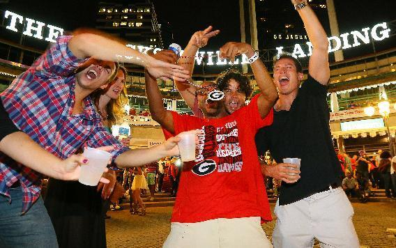 Georgia football fan Tommy Moore, 31, Athens, finds himself surrounded by Florida Gators fans on The Jacksonville Landing on Friday, Nov. 1, 2013, in Jacksonville, Fla. Florida and Georgia play Saturday in an NCAA college football game in jacksonville. (AP Photo/Atlanta Journal-Constitution, Curtis Compton)