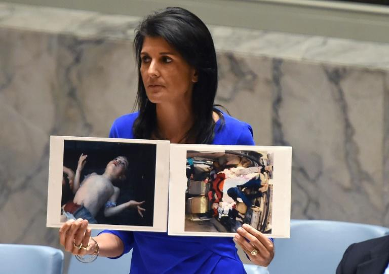 US Ambassador to the UN Nikki Haley holds photos of victims as the UN Security Council meets in an emergency session in April about a suspected deadly chemical attack that killed civilians, including children, in Syria