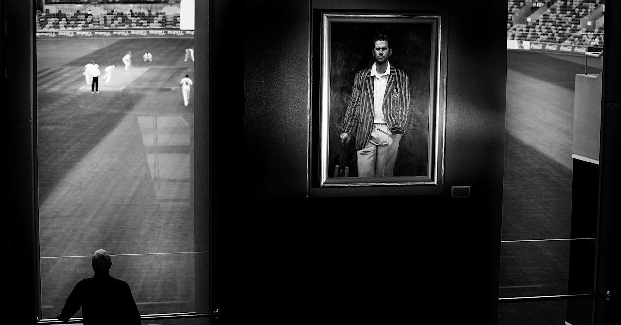 HOBART, AUSTRALIA - MARCH 15: (EDITOR'S NOTE: Image shot in black and white. Colour version not available.) A portrait of Ricky Ponting is displayed in the foyer of the Tasmanian Cricket Museum as a man watches play during day two of the Sheffield Shield match between the Tasmania Tigers and the Victoria Bushrangers at Blundstone Arena on March 15, 2013 in Hobart, Australia.  (Photo by Mark Nolan/Getty Images)