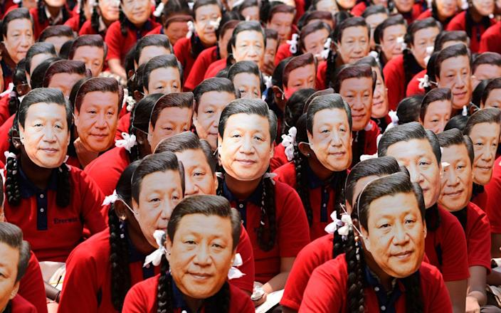Indian school students wear masks of President Xi Jinping ahead of a summit between China and India in 2019 - ARUN SANKAR /AFP