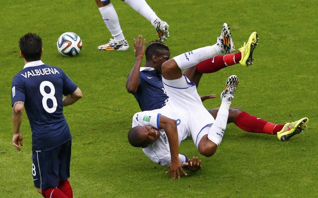 France's Mathieu Valbuena (L) looks on as France's Paul Pogba and Wilson Palacios of Honduras (front) fall after committing a foul on each other during their 2014 World Cup Group E soccer match at the Beira Rio stadium in Porto Alegre, June 15, 2014. Both received a yellow card from the referee. REUTERS/Marko Djurica (BRAZIL - Tags: SOCCER SPORT TPX IMAGES OF THE DAY WORLD CUP)