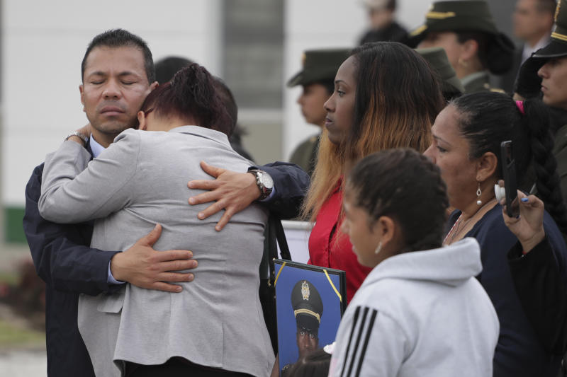 Relatives embrace during a ceremony marking one year since a car bomb attack on the police academy in Bogota, Colombia, Monday, Jan. 20, 2020, during the inauguration of a regional anti-terrorism summit attended by Colombian President Ivan Duque, US State Secretary Mike Pompeo and Venezuela's opposition leader Juan Guaido. Colombian government blamed rebels of the National Liberation Army, ELN, for the bombing that killed at least 21 people on Jan. 17, 2019. (AP Photo/Ivan Valencia)
