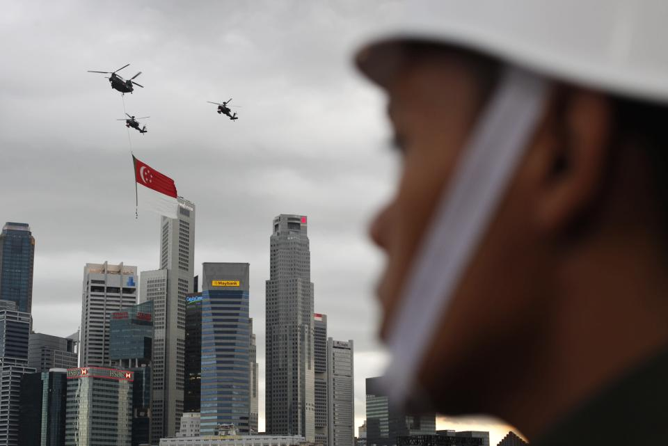 Helicopters fly past with a Singapore flag during Singapore's 49th National Day Parade at the floating platform in Marina Bay August 9, 2014. REUTERS/Edgar Su (SINGAPORE - Tags: SOCIETY ANNIVERSARY MILITARY)