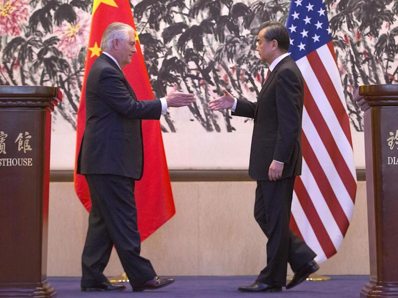 Chinese Foreign Minister Wang Yi (R) shakes hands with US Secretary of State Rex Tillerson after a joint press conference in Beijing, China (Getty)